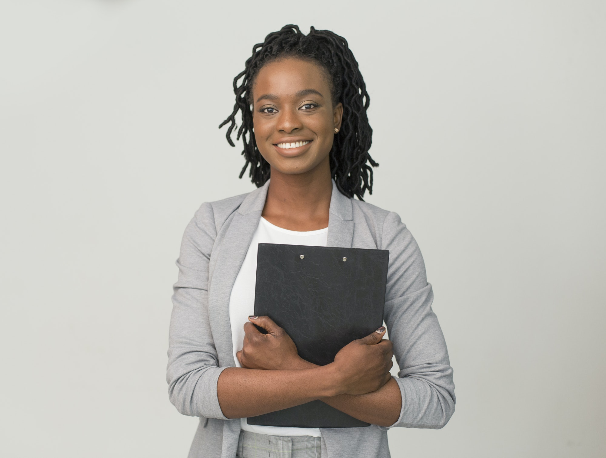 Smiling African American Business Lady Holding Folder, Studio Shot