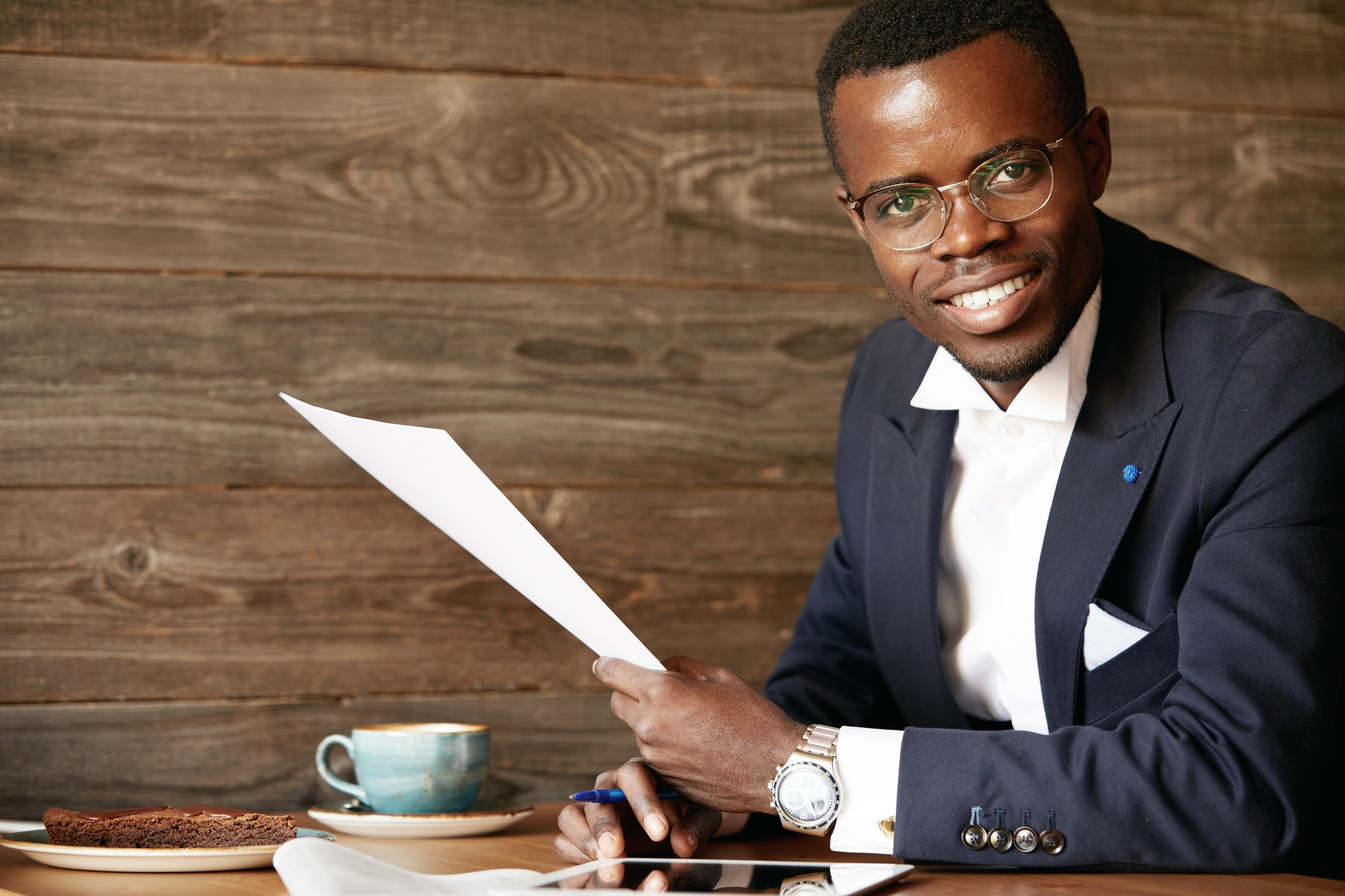 Success and achievement. Happy African businessman in glasses looking the camera with cheerful ultra