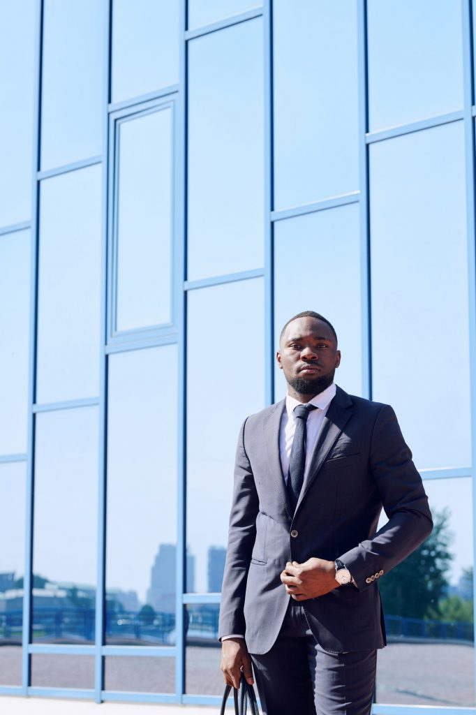 Young African business professional in formalwear standing against building